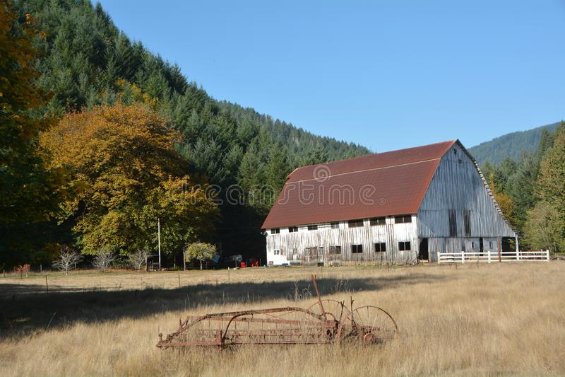 White barn with antique farm equipment in Southwest Oregon. This is a white barn with antique farm equipment in Southwest Oregon. It is bordered with a forest stock photography