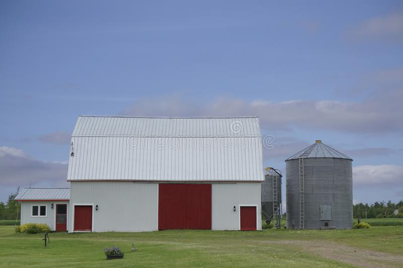 White barn with red doors under a blue sky. Family farm in Prince Edward Island, Canada with a barn and silos royalty free stock image