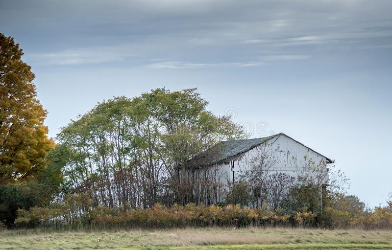 White barn sits against a colorful fall landscape stock photos