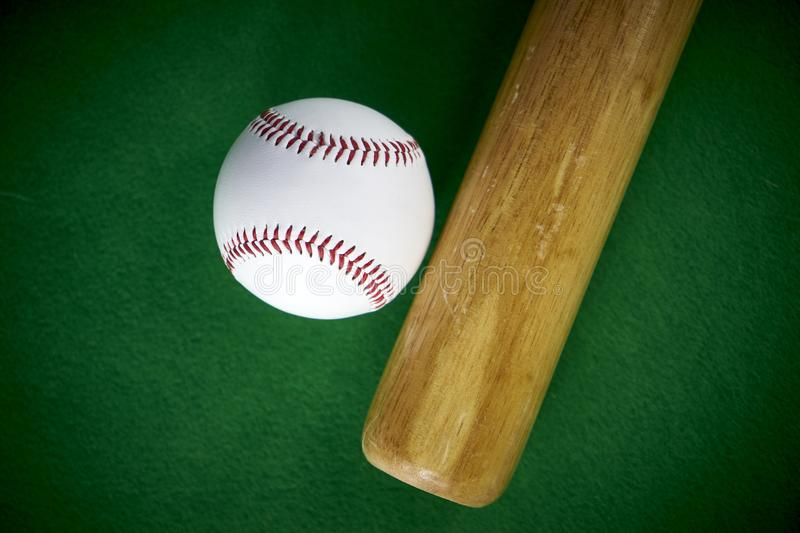 White Baseball ball and wooden bit isolated on green felt background stock images
