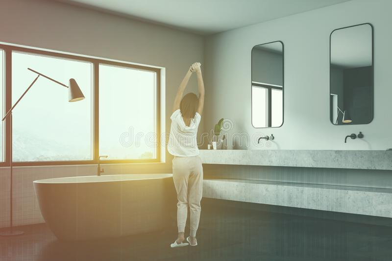 White bathroom corner, tub and double sink, woman stock photos