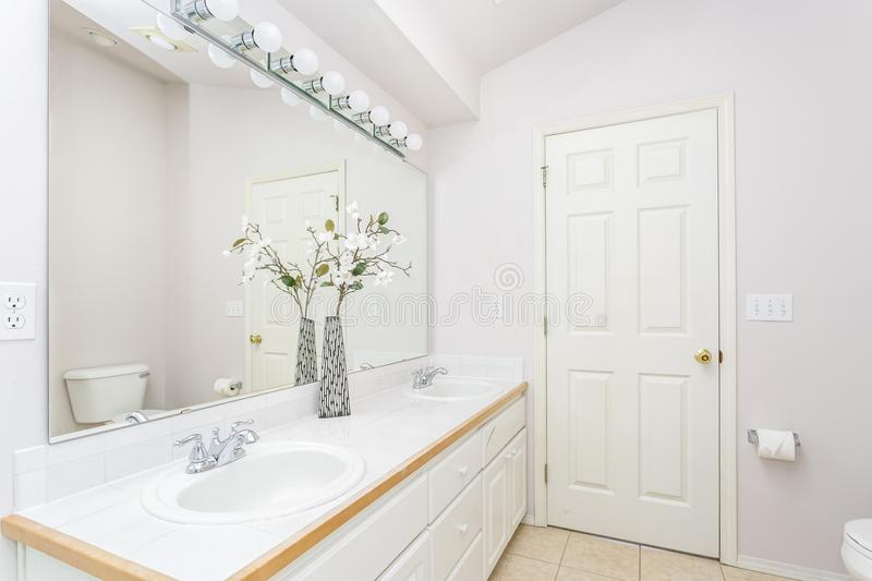 White bathroom interior with vaulted ceiling. White bathroom interior with double sink vanity and vaulted ceiling royalty free stock photo