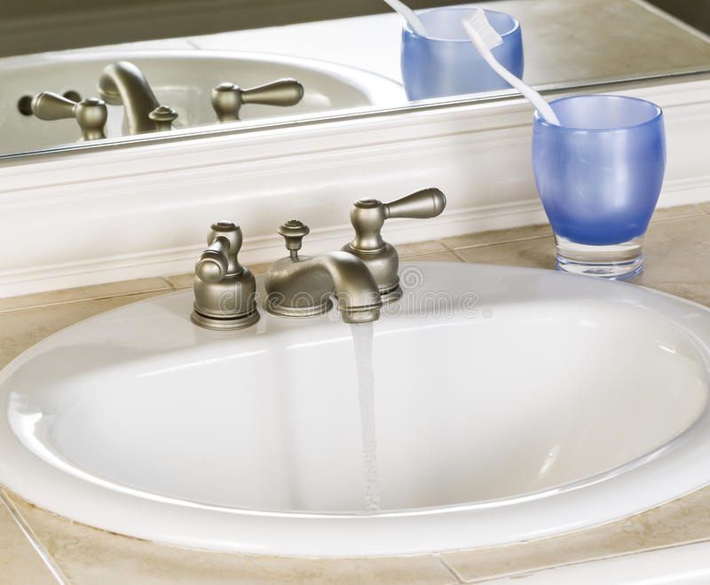 White Bathroom Sink And Faucet In Open Position With Clean Water ...