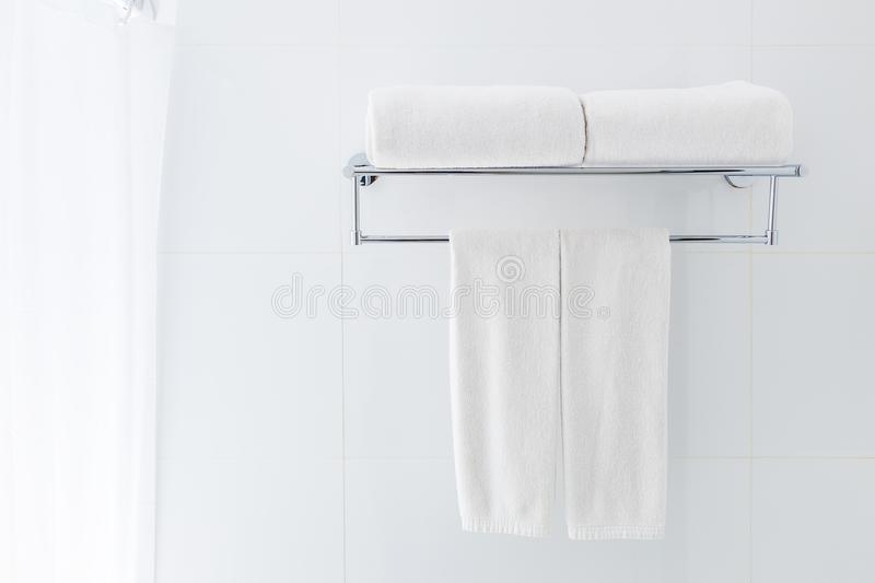White bathroom towels hanging on the rack in a white bathroom ne. Ar shower, good for clean and fresh theme or refresh concept stock photography
