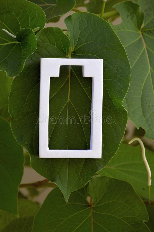 White battery icon on green leaves. Of tropical tree, White battery symbol placed on a green leaf. White object in nature vegetation. Save energy concept royalty free stock photos