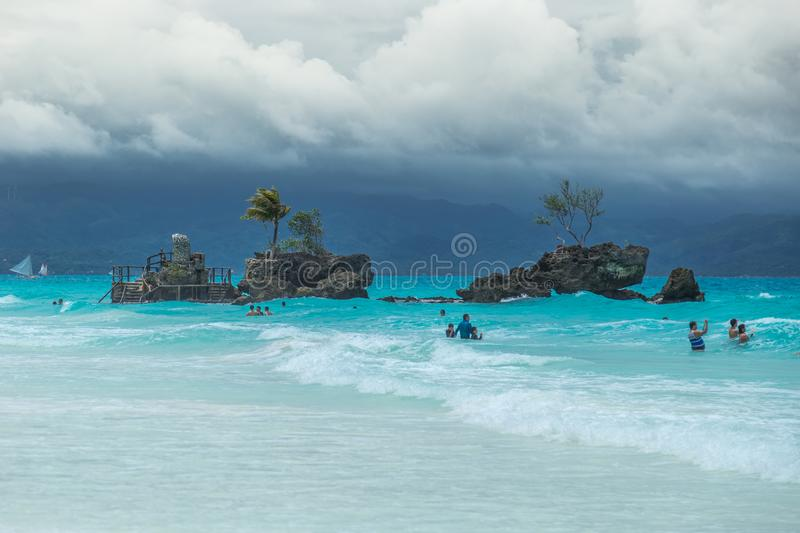 White Beach of Boracay and people swim at turquoise azure Sea on a cloudy day near Grotto Willy`s Rock upon which stands stock photos