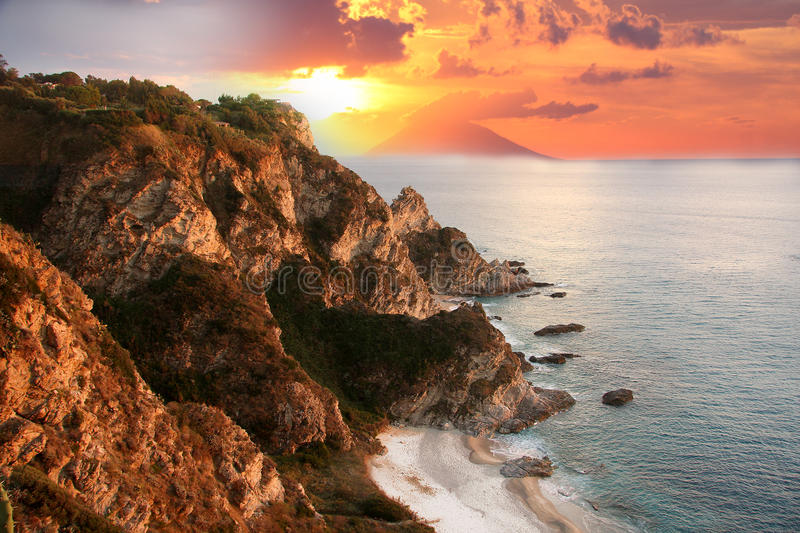 White beach in Calabria, Italy. Sunset over the cliff in Calabria against Stromboli, Italy stock photo