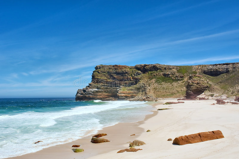 White beach with red rocks next to misty mountains stock photography