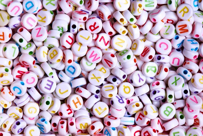 White beads with multicolored English letters close-up. White beads with multicolored English letters royalty free stock photography