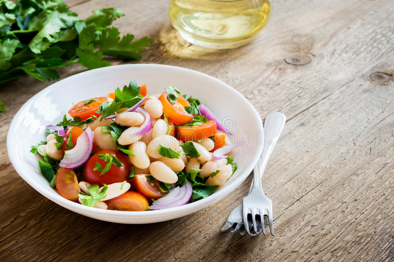 White Bean Salad. With Cherry Tomatoes, Onion and Parsley on wooden background, copy space - healthy homemade organic vegetarian vegan diet protein salad meal stock photos
