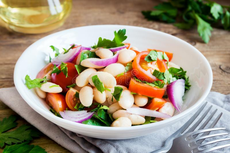 White Bean Salad. With Cherry Tomatoes, Onion and Parsley on wooden background, copy space - healthy homemade organic vegetarian vegan diet protein salad meal stock images