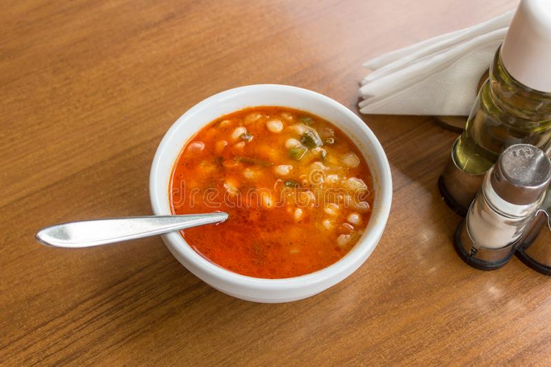 White beans in tomato sauce in a bowl with a spoon in on wooden table at a restaurant stock images