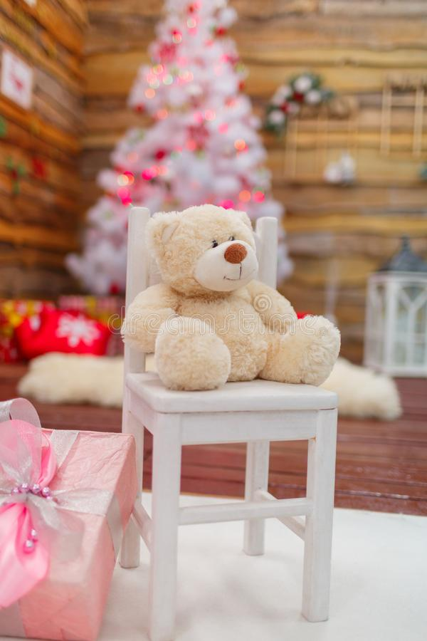 White bear on the chair in the festive room. White bear next to a chair in a festive room on a blurred background of a Christmas tree with gifts stock images