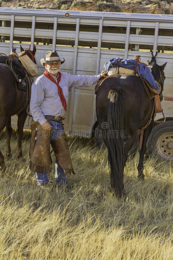 White Bearded Cowboy by his Horse stock photography