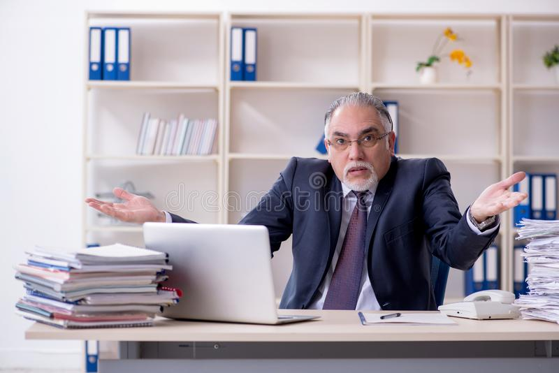 The white bearded old businessman employee unhappy with excessive work stock images