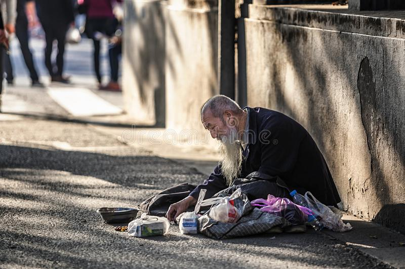 White-bearded old man begging in downtown Xinjiekou. In December 2017, a white-bearded old man sitting on the ground begging in the downtown area of Xinjiekou royalty free stock images