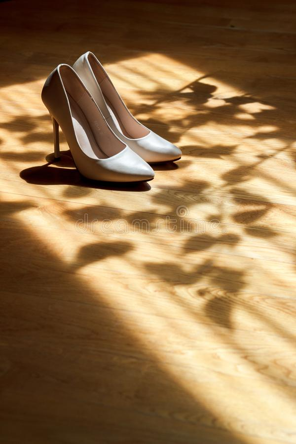 White beautiful wedding shoes in shade in sunlight. Wedding shoes, partially illuminated by sunlight, partially in the shade royalty free stock photography