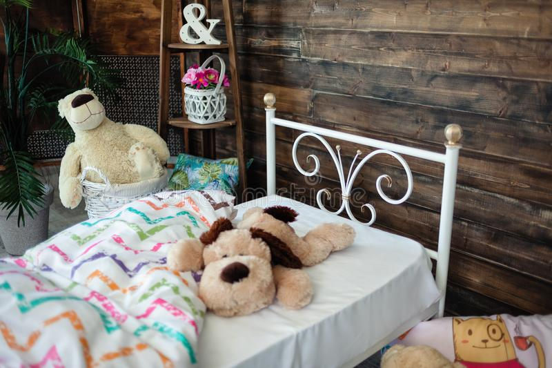White forged crib. White bed forged wrought iron. Bed is covered with white linens. In the frame of soft toys royalty free stock images