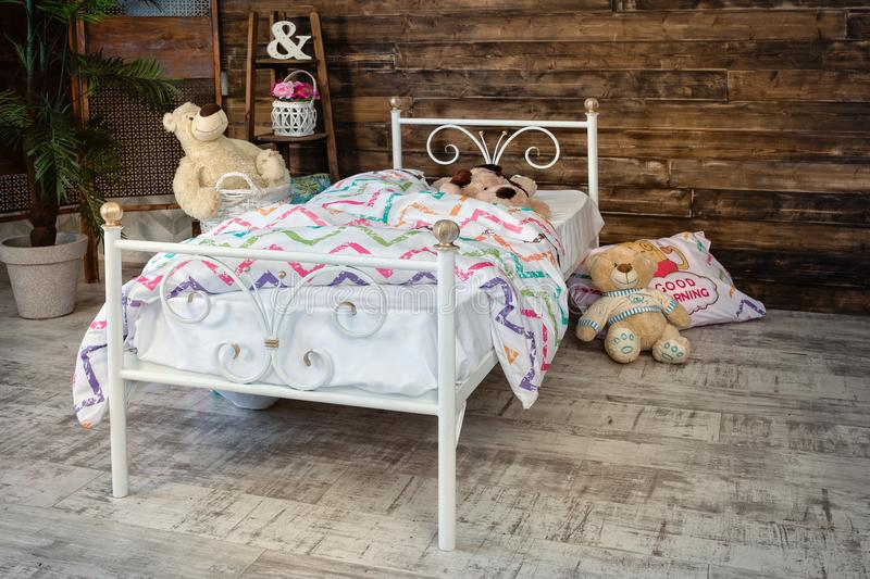 White forged crib. White bed forged wrought iron. Bed is covered with white linens. In the frame of soft toys royalty free stock photos