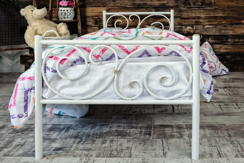 White forged crib. White bed forged wrought iron. Bed is covered with white linens. In the frame of soft toys royalty free stock photo
