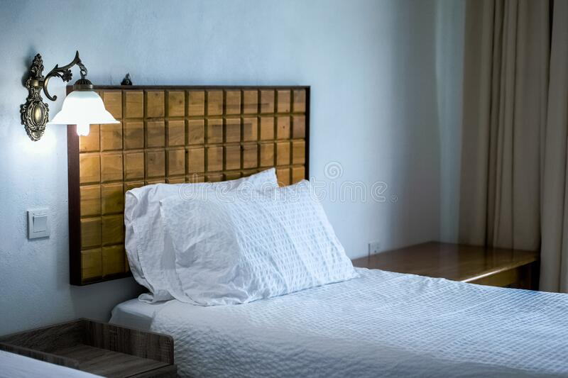 White Bedding Cover Beside Brown Wooden Side Table royalty free stock image