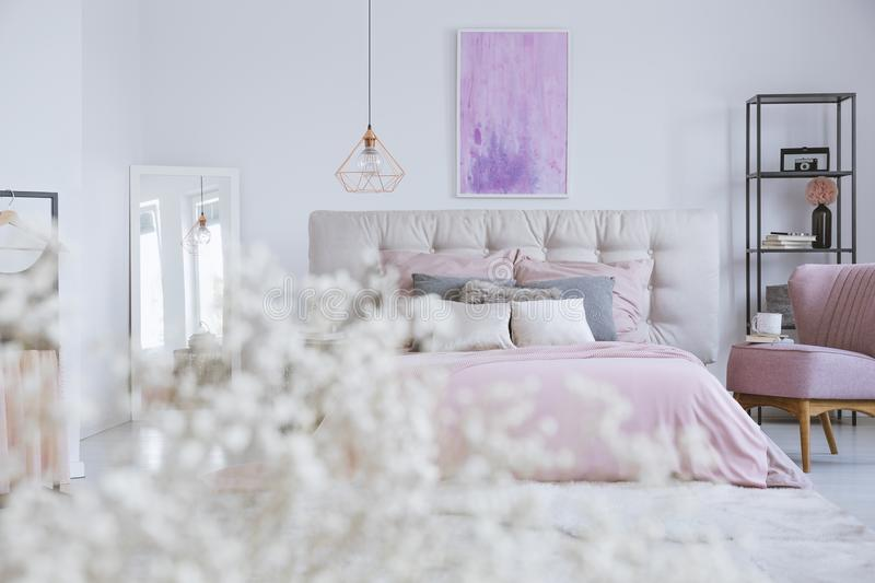 White bedhead of double bed. Wide white bedhead of double bed with pink bedsheets and decorative pillows in simple room interior stock photo