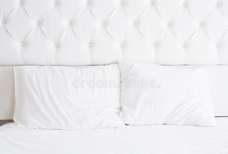 White bedroom interior design with bed and blank pillows. Bedding relax time. Mock up. Copy space stock photo