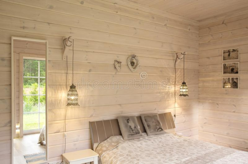 White bedroom interior in a house with white wood trim with furniture, a bed, lamps, a mirror. Scandinavian style. Real photo of white bedroom interior in a royalty free stock photo