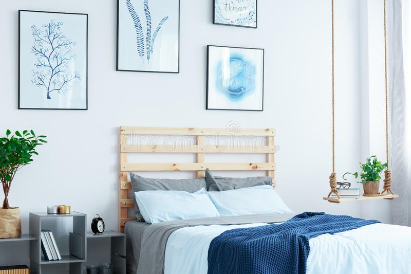 White bedroom with wood bed. Swing shelf, wall posters, plants royalty free stock photo