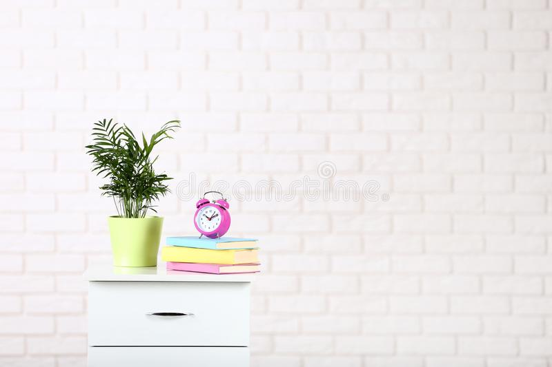 Bedside table with books, alarm clock stock photos