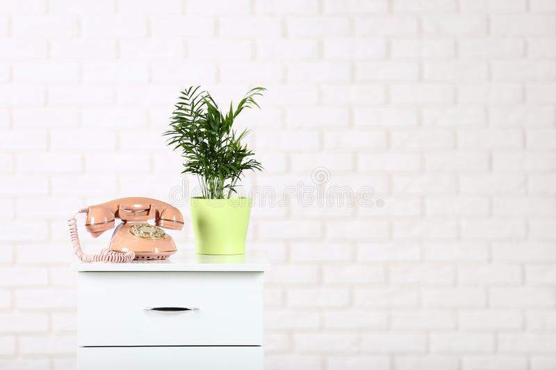 Bedside table with telephone and green plant royalty free stock images