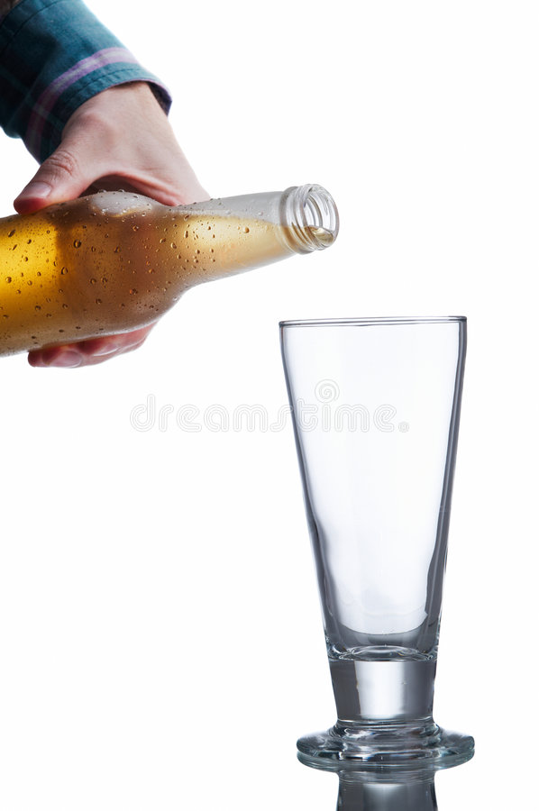 White beer bottle and glass. Non-glossy white beer bottle, back lighted showing a glowing golden beer content, drops and condensation about to pour beer on an stock images