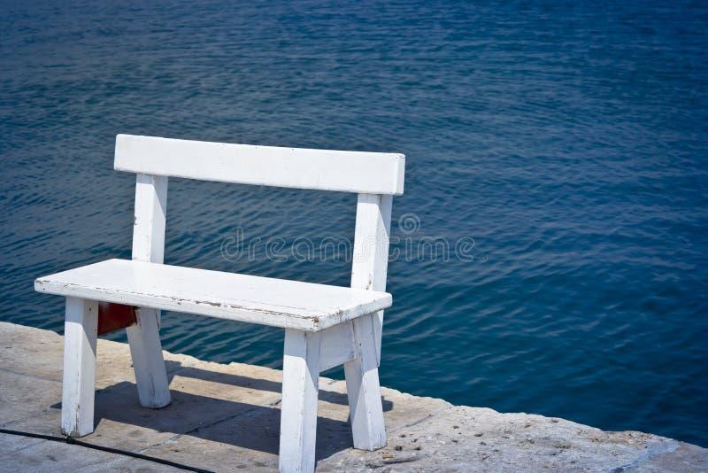 White bench on the coast stock photo