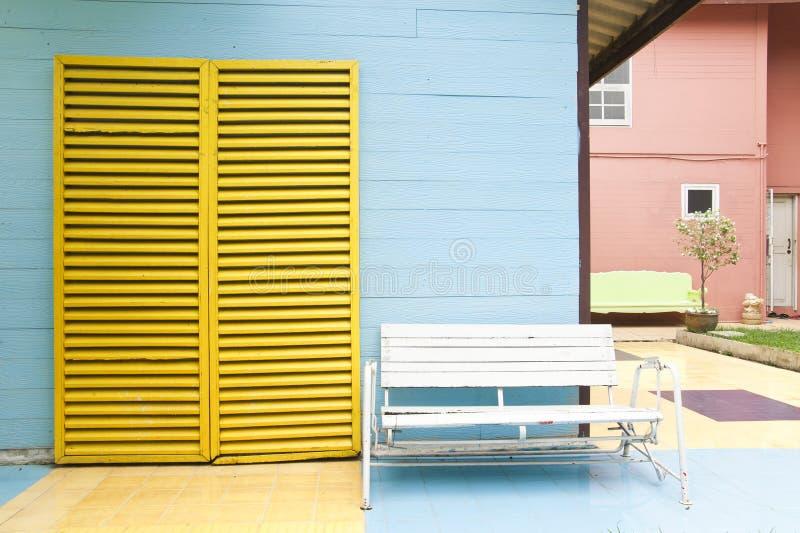 White bench and yellow door stock photo
