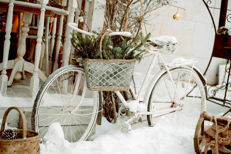 White bicycle with a basket with fir branches outside, New Year`s decoration for the holiday. Rustic style stock photo