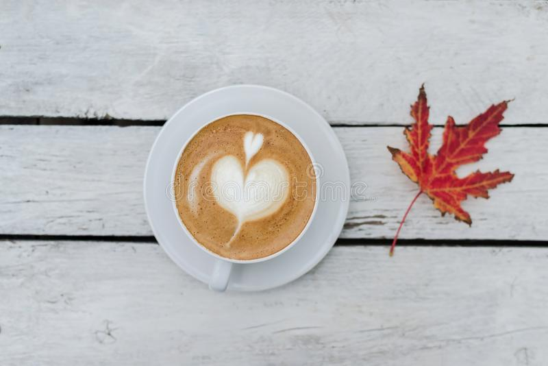 White big cup of coffee with art on white wooden table and orange autumn leaf with copy space. stock photography