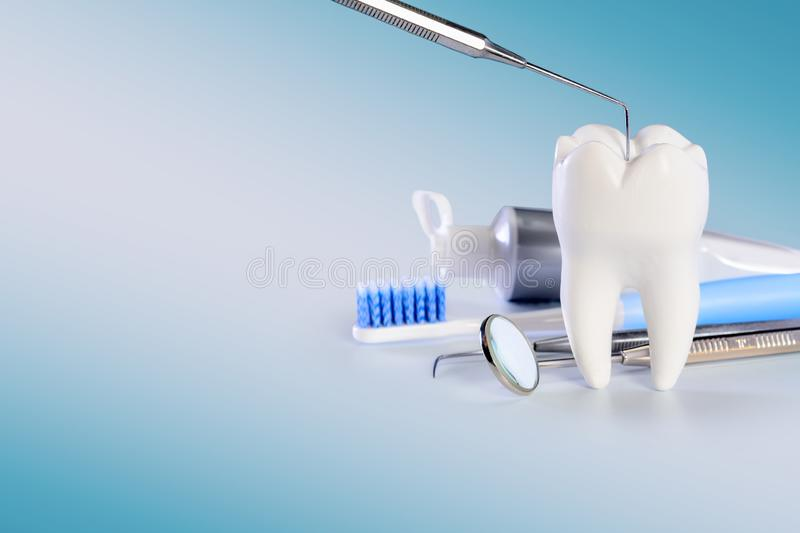White big healthy tooth and different tools for dental care, on gradient dental background with dental probe. White big healthy tooth and different tools for royalty free stock photography