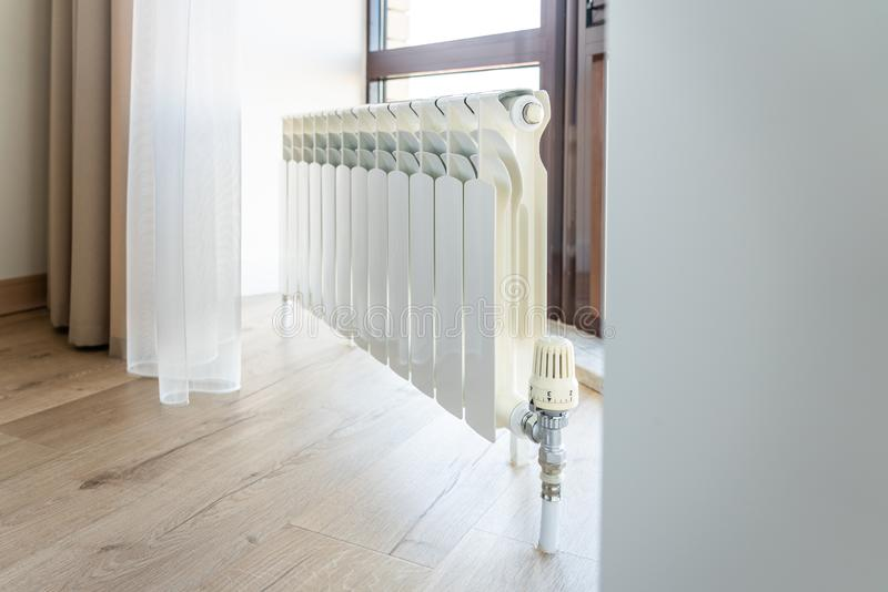 White big radiator near window in modern room royalty free stock images