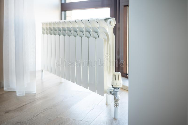 White big radiator with thermostat near window in modern room royalty free stock photos