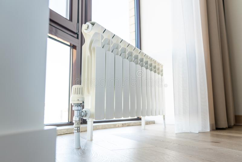 White big radiator with thermostat near window in modern room stock photo