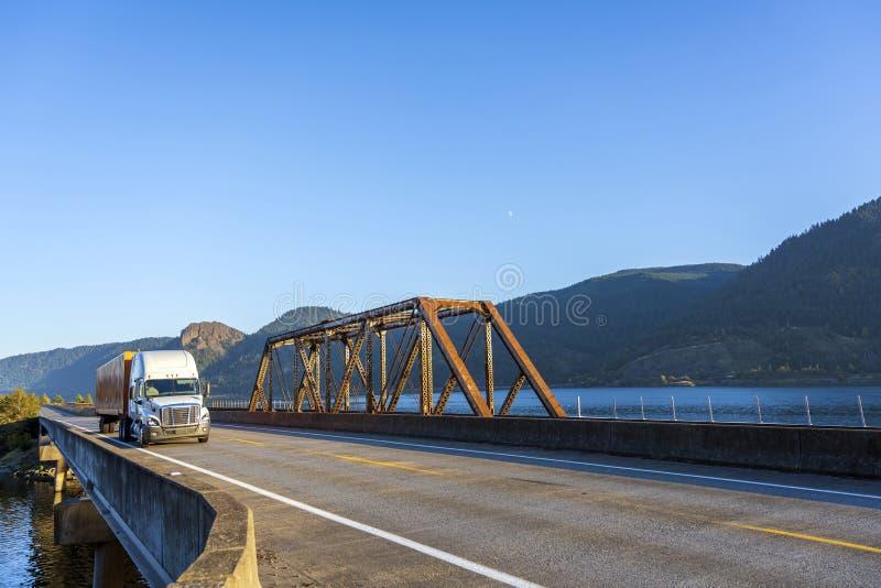White big rig semi truck transporting cargo in orange semi trail. White big rig bonnet semi truck transporting commercial cargo in dry van orange semi trailer stock images