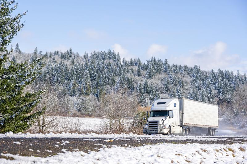 White big rig long haul semi truck with refrigerator semi trailer running on the winding winter snowy road with forest. Big rig long haul white semi truck royalty free stock image