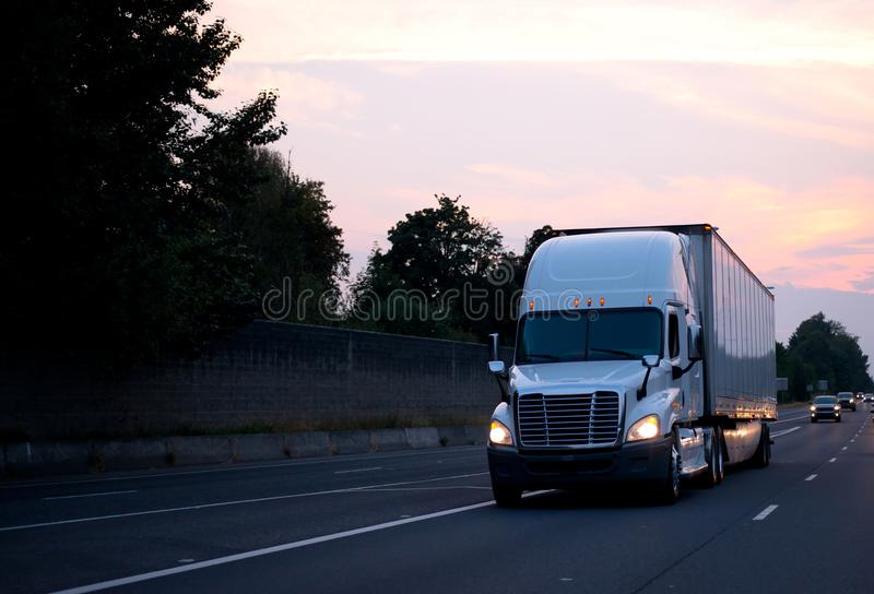 White big rig semi truck with dry van trailer driving on evening stock photo
