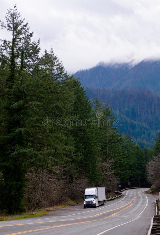 White big rig semi truck with reefer trailer stand on gorgeous r. White big rig American semi truck with reefer trailer stand on shoulder of a gorgeous road with royalty free stock photos