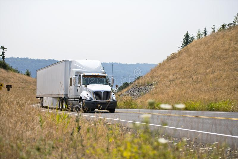 White big rig semi truck transporting goods in dry van semi trailer going on spectacular winding road between the hills with royalty free stock images