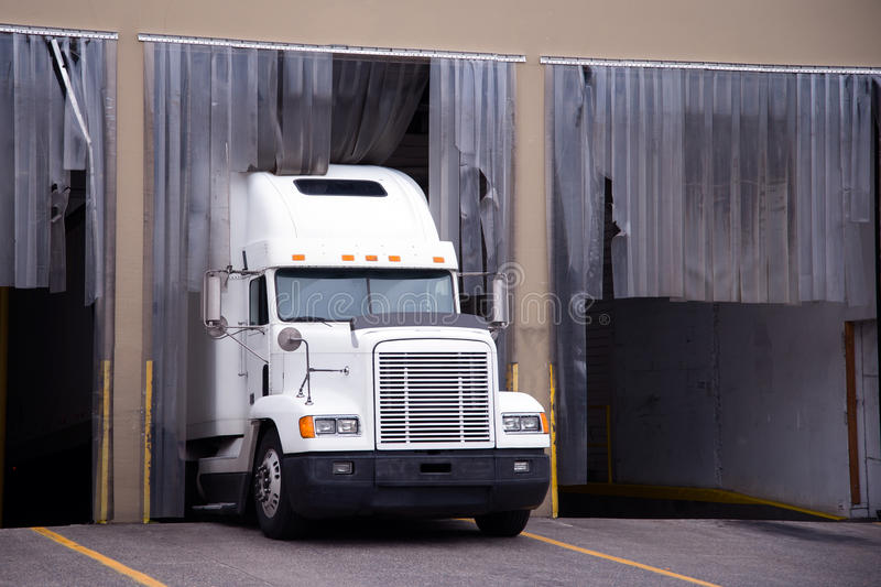 White big rig semi truck in warehouse dock stock photos