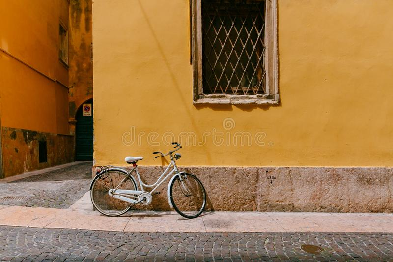 White bike parked agaisnt yellow wall in the street of Verona, Italy royalty free stock photo
