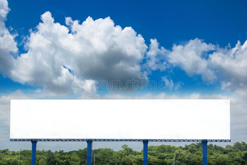 White billboard blank canvas mockup for outdoor advertising poster or blank billboard at day time. And cloud and blue sky background royalty free stock photography