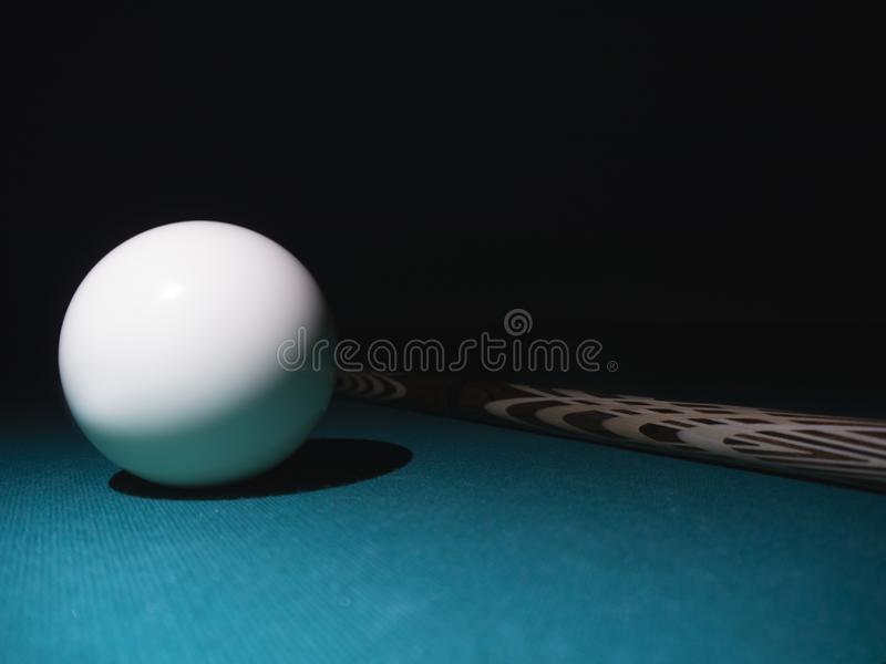 White billiard ball a cue on a table. Black background.  royalty free stock photography