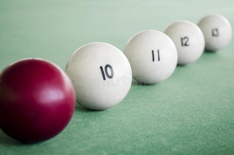 White billiard balls and cue ball for billiards. A row of balls on a pool table.  stock photos